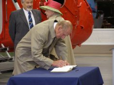The Duke of Edinburgh signs the Visitors Book