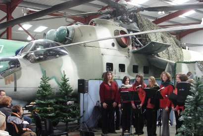 Lyrica sing carols beside the Mi-24, 'Hind'.